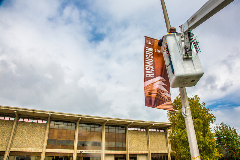 """A facilities crew member hangs a new location banner near the Rasmuson Library on the Fairbanks campus.  <div class=""""ss-paypal-button"""">Filename: CAM-13-3920-11.jpg</div><div class=""""ss-paypal-button-end"""" style=""""""""></div>"""