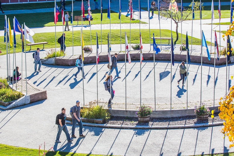 "Students walk through the circle of flags in Cornerstone Plaza on the Fairbanks campus.  <div class=""ss-paypal-button"">Filename: CAM-12-3541-52.jpg</div><div class=""ss-paypal-button-end"" style=""""></div>"