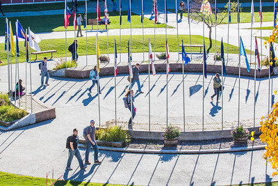 Students walk through the circle of flags in Cornerstone Plaza on the Fairbanks campus.  Filename: CAM-12-3541-52.jpg