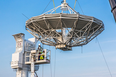 A crew from Texas helps install an 11-meter antenna operated by UAF's Alaska Satellite Facility at its location on West Ridge. Once fully operational, the dish will gather data from spacecraft about land surface, biosphere, atmosphere, oceans and outer space. It's one of several strategically placed antennas that can capture data from polar-orbiting satellites several times per day.  Filename: CAM-13-3903-036.jpg