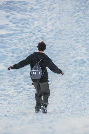 A student slides down the hill by the Patty Center during a warm January afternoon on the Fairbanks campus.  Filename: CAM-14-4039-92.jpg