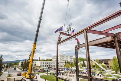 Iron workers with Davis Constructors prepare to place the final steel beam into position in UAF's new engineering facility this afternoon while a crowd of university, legislative and business leaders look on. The final piece of steel is topped with Alaska and U.S. flags and, following an ancient  Scandinavian tradition, a small tree.  Filename: CAM-14-4199-110.jpg