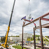 "Iron workers with Davis Constructors prepare to place the final steel beam into position in UAF's new engineering facility this afternoon while a crowd of university, legislative and business leaders look on. The final piece of steel is topped with Alaska and U.S. flags and, following an ancient  Scandinavian tradition, a small tree.  <div class=""ss-paypal-button"">Filename: CAM-14-4199-110.jpg</div><div class=""ss-paypal-button-end""></div>"