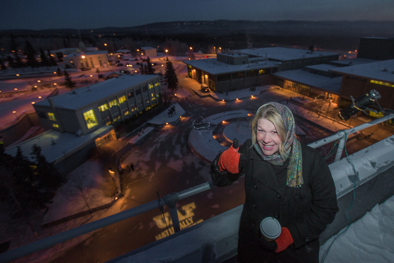 "UAF Marketing manager Darcy Herrod gives the thumbs up sign after helping place the ""Naturally Inspiring"" tagline light on top of the Gruening Building on a cold November morning.  <div class=""ss-paypal-button"">Filename: CAM-12-3665-25.jpg</div><div class=""ss-paypal-button-end"" style=""""></div>"