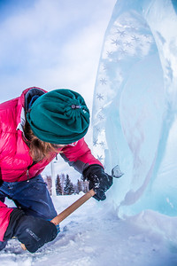 Ronald Daanen, a research assistant professor with UAF's Institute of Northern Engineering, puts some finishing touches on an ice carving of a hibernating bear in front of the University of Alaska Museum of the North Monday afternoon.  Filename: CAM-13-3701-1.jpg