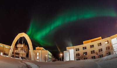 The aurora borealis dances across the night sky above the annual ice arch on UAF's campus.  Filename: CAM-12-3324-27.jpg