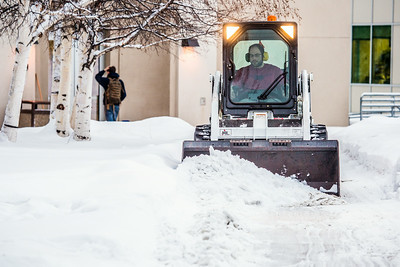 A Facilities Services crew member clears fresh snow from walkways around the Fairbanks campus on the first day of classes in the Spring 2014 semester.  Filename: CAM-14-4038-11.jpg