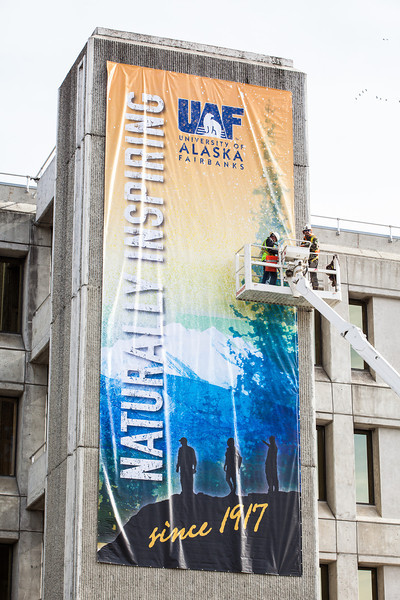 "Construction workers attach a banner on the side of the Gruening Building.  <div class=""ss-paypal-button"">Filename: CAM-13-3921-45.jpg</div><div class=""ss-paypal-button-end"" style=""""></div>"