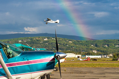 A rainbow appears behind a small plane as it takes off from the Fairibanks International Airport on a summer morning.  Filename: CAM-12-3497-021.jpg