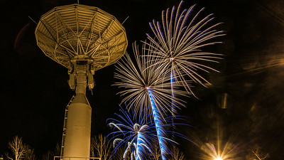 Fireworks illuminate the Alaska Satellite Facility's 11-meter antenna on West Ridge during the annual New Year's Eve Sparktacular.  Filename: CAM-13-4028-52.jpg
