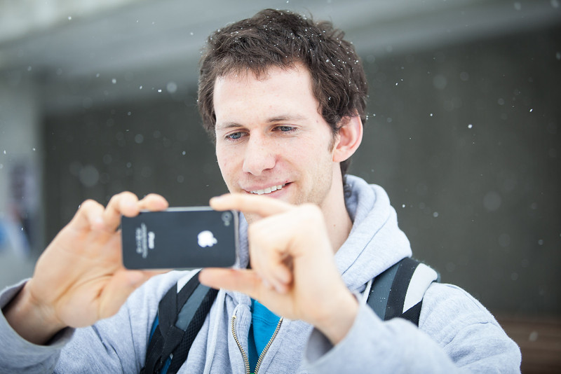 """Shaun Nesheim takes a photo with his phone in front of the Gruening building during the first snowfall of the semester in mid-October 2012.  <div class=""""ss-paypal-button"""">Filename: CAM-12-3589-14.jpg</div><div class=""""ss-paypal-button-end"""" style=""""""""></div>"""