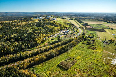 An aerial view of UAF looking east toward Fairbanks at about 11:15 a.m. on Sept. 10, 2016. The experiment farm operated by the School of Natural Resources and Extension is featured in the center of this photo.  Filename: CAM-16-4992-004.jpg