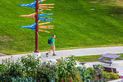 A pedestrian makes his way past the distinctive milepost sign on UAF's West Ridge.  Filename: CAM-12-3505-10.jpg