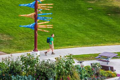 A pedestrian makes his way past the distinctive milepost sign on UAF's West Ridge.  Filename: CAM-12-3505-10.jpg