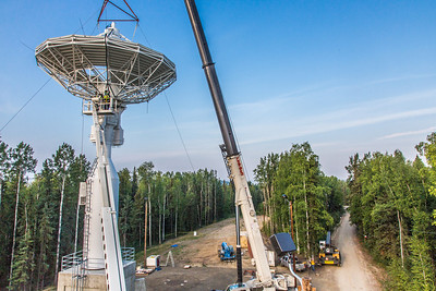 A crew from Texas helps install an 11-meter antenna operated by UAF's Alaska Satellite Facility at its location on West Ridge. Once fully operational, the dish will gather data from spacecraft about land surface, biosphere, atmosphere, oceans and outer space. It's one of several strategically placed antennas that can capture data from polar-orbiting satellites several times per day.  Filename: CAM-13-3903-061.jpg