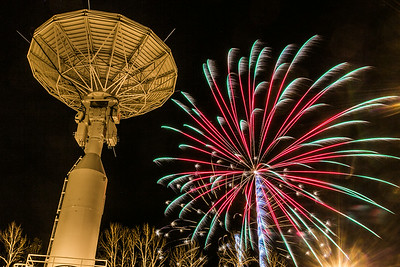 Fireworks explode near the Alaska Satellite Facility's new 11-meter antenna on UAF's West Ridge during the annual New Year's Eve Sparkatular event sponsored by local businesses.  Filename: CAM-13-4028-37.jpg