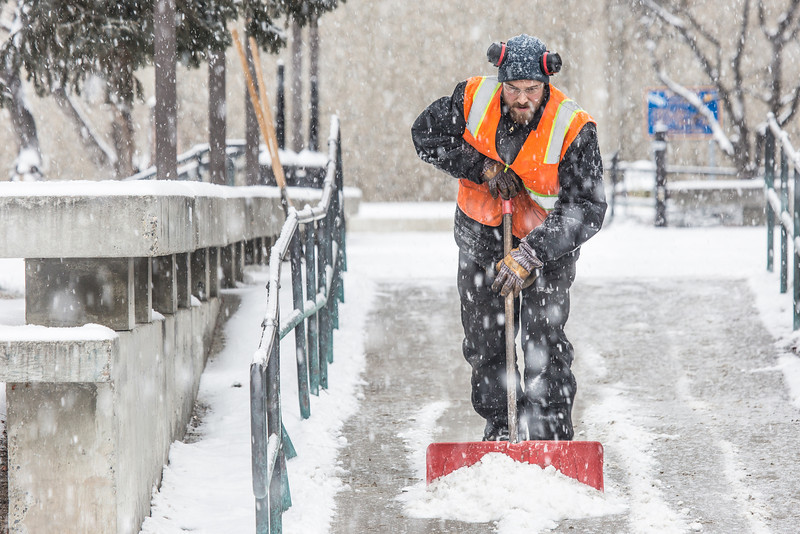 """Maintenance crew foreman Raif Kennedy works to clear a path in front of the Rasmuson Library during a brief but heavy snowfall Nov. 5 on the Fairbanks campus.  <div class=""""ss-paypal-button"""">Filename: CAM-13-3993-14.jpg</div><div class=""""ss-paypal-button-end"""" style=""""""""></div>"""