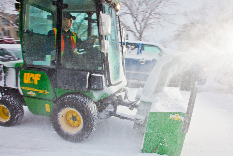 """Paul Dick, an equipment operator for Facilities Services, blows snow from a campus sidewalk after a November dusting.  <div class=""""ss-paypal-button"""">Filename: CAM-11-3213-26.jpg</div><div class=""""ss-paypal-button-end"""" style=""""""""></div>"""