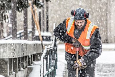 Maintenance crew foreman Raif Kennedy works to clear a path in front of the Rasmuson Library during a brief but heavy snowfall Nov. 5 on the Fairbanks campus.  Filename: CAM-13-3993-10-Edit.jpg