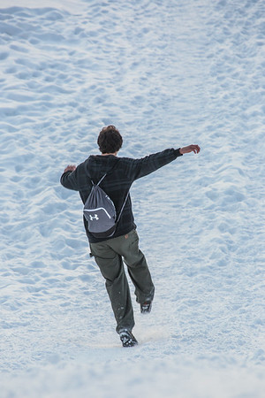 A student slides down the hill by the Patty Center during a warm January afternoon on the Fairbanks campus.  Filename: CAM-14-4039-93.jpg