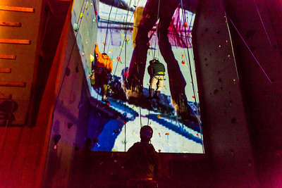 A video image is projected on UAF's outdoor climbing wall while a pair of student climbers make their up the route during a late night promotional multi-media production.  Filename: CAM-13-3925-53.jpg
