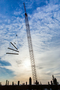 A 220-foot crane lifts steel beems into position as workers complete the superstructure for the third floor of the new engineering facility in April 2014.  Filename: CAM-14-4131-39.jpg