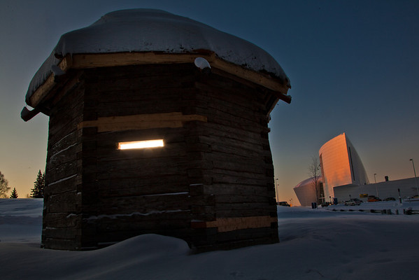 """The 1841 Russian blockhouse stands at first light on its new foundation near the University of Alaska Museum of the North. It was the first structure built by the Russian-American Company at Kolmakovsky Redoubt near Aniak. It is one of the oldest Russian-era structures in Alaska. In 1929, the blockhouse was disassembled and moved to Fairbanks where last summer a preservation team completed work on reattaching an updated roof outfitted with tundra sod and tamarack poles.  <div class=""""ss-paypal-button"""">Filename: CAM-12-3277-61.jpg</div><div class=""""ss-paypal-button-end"""" style=""""""""></div>"""