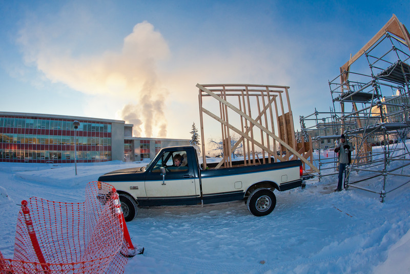 """Engineering students Rowland Powers (in pickup) and Andy Chamberlain unload pieces of the superstructure in preparation for laying ice and building the 2012 ice arch. The construction of an ice arch on campus has been a tradition among engineering majors at UAF for more than 50 years.  <div class=""""ss-paypal-button"""">Filename: CAM-12-3261-24.jpg</div><div class=""""ss-paypal-button-end"""" style=""""""""></div>"""