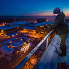"""Jon Huff with AUP mounts and adjusts the light projecting the """"Naturally Inspiring"""" tagline down on the campus from atop the Gruening Building on a cold November morning.  <div class=""""ss-paypal-button"""">Filename: CAM-12-3665-15.jpg</div><div class=""""ss-paypal-button-end"""" style=""""""""></div>"""