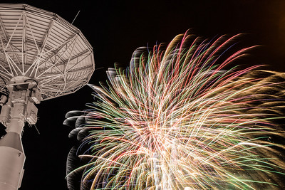 Fireworks illuminate the Alaska Satellite Facility's 11-meter antenna on West Ridge during the annual New Year's Eve Sparktacular.  Filename: CAM-13-4028-60.jpg