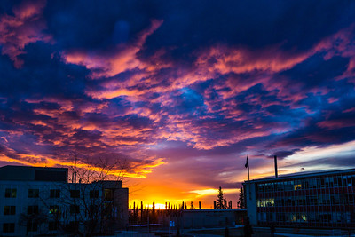 A dramatic sunrise lights up the sky between the Duckering and Bunnell buildings on a late October morning.  Filename: CAM-13-3976-13.jpg