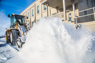 A Facilities Services crew member uses some heavy equipment to sweep the sidewalk in front of Signers' Hall after a late winter snowfall.  Filename: CAM-13-3786-21.jpg