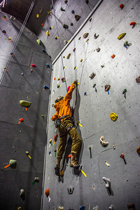 A climber chooses his route during an evening event on UAF's climbing wall.  Filename: CAM-13-3925-2.jpg