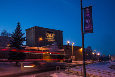 """The tagline """"Naturally Inspiring"""" is illuminated on the outside wall of UAF's Salisbury Theatre on a cold winter evening.  Filename: CAM-12-3678-8.jpg"""