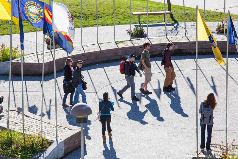 """Students finished with their class in the Bunnell building walks accross the Circle of Flags on a September afternoon.  <div class=""""ss-paypal-button"""">Filename: CAM-12-3543-21.jpg</div><div class=""""ss-paypal-button-end"""" style=""""""""></div>"""