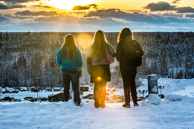 Three students pause to watch a January sunset during a warm afternoon on the Fairbanks campus.  Filename: CAM-14-4039-60.jpg