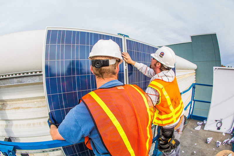 """Mike Stagno, left, and Eddie Davidson with ABS Alaskan Inc. install solar panels on the south side of the SRC.  <div class=""""ss-paypal-button"""">Filename: CAM-12-3568-69.jpg</div><div class=""""ss-paypal-button-end"""" style=""""""""></div>"""