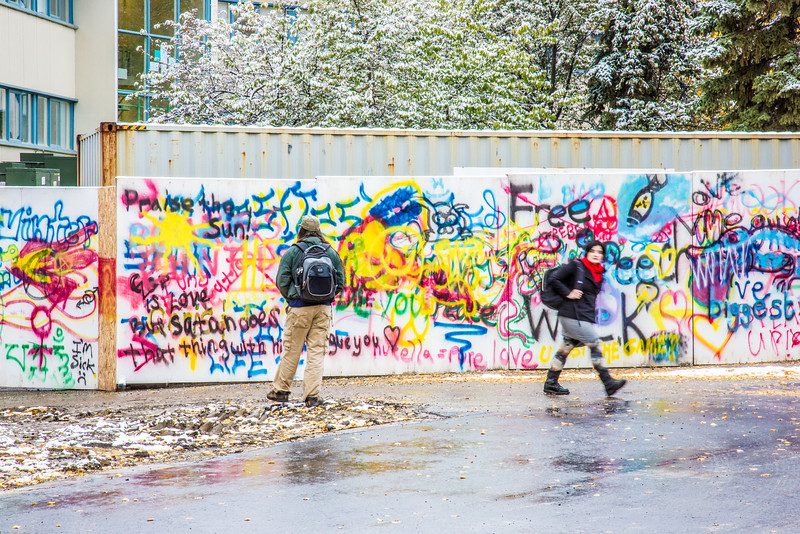 "A student stops to reflect on some new additions to the graffiti wall used to isolate the construction zone near Wood Center.  <div class=""ss-paypal-button"">Filename: CAM-13-3944-32.jpg</div><div class=""ss-paypal-button-end"" style=""""></div>"