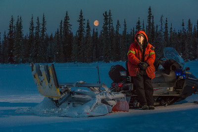 Ski trails manager Jason Garron takes a break on frozen Smith Lake while grooming the skate ski track on the UAF trails early on a cold February morning.  Filename: CAM-16-4818-45.jpg