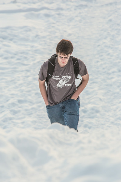 """A student walks up the hillside near the Patty Center during a warm January afternoon on the Fairbanks campus.  <div class=""""ss-paypal-button"""">Filename: CAM-14-4039-42.jpg</div><div class=""""ss-paypal-button-end""""></div>"""