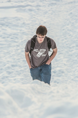 A student walks up the hillside near the Patty Center during a warm January afternoon on the Fairbanks campus.  Filename: CAM-14-4039-42.jpg