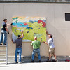 "Facility Services hangs ""The Mumbles Between Us"" by Christopher Green, a mural commissioned by KSUA Student Radio and TV outside the Wood Center.  <div class=""ss-paypal-button"">Filename: CAM-12-3449-7.jpg</div><div class=""ss-paypal-button-end"" style=""""></div>"