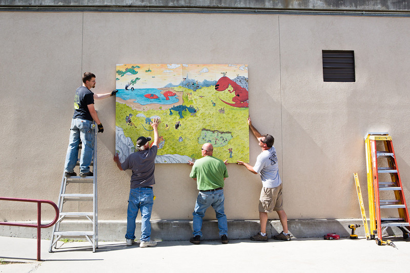 """Facility Services hangs """"The Mumbles Between Us"""" by Christopher Green, a mural commissioned by KSUA Student Radio and TV outside the Wood Center.  <div class=""""ss-paypal-button"""">Filename: CAM-12-3449-7.jpg</div><div class=""""ss-paypal-button-end"""" style=""""""""></div>"""