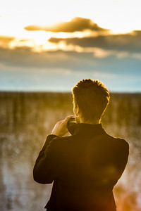A student pauses to snap a photo of a January sunset on the Fairbanks campus.  Filename: CAM-14-4039-83.jpg