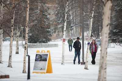 Students walk on the freshly plowed and gravelled pavement by Facility Services at the first snowfall of the semester in mid-October 2012.  Filename: CAM-12-3589-47.jpg