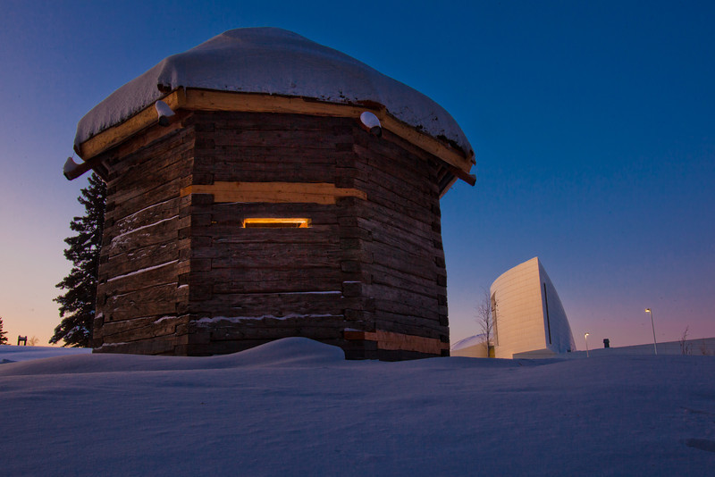 "The 1841 Russian blockhouse stands at first light on its new foundation near the University of Alaska Museum of the North. It was the first structure built by the Russian-American Company at Kolmakovsky Redoubt near Aniak. It is one of the oldest Russian-era structures in Alaska. In 1929, the blockhouse was disassembled and moved to Fairbanks where last summer a preservation team completed work on reattaching an updated roof outfitted with tundra sod and tamarack poles.  <div class=""ss-paypal-button"">Filename: CAM-12-3277-19.jpg</div><div class=""ss-paypal-button-end"" style=""""></div>"
