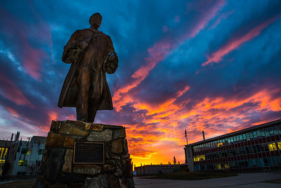 A dramatic sunrise lights up the sky behind the statue of Charles Bunnell on a late October morning.  Filename: CAM-13-3976-9.jpg