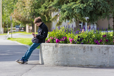 A student checks in with his smart phone while waiting for a friend in front of Wood Center on the Fairbanks campus.  Filename: CAM-15-4638-061.jpg