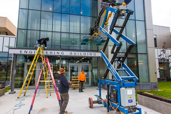 """A crew from Hoffer Glass installs panels on the entry way to the new engineering building on the Fairbanks campus in August 2015.  <div class=""""ss-paypal-button"""">Filename: CAM-15-4634-034.jpg</div><div class=""""ss-paypal-button-end""""></div>"""