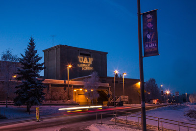 "The tagline ""Naturally Inspiring"" is illuminated on the outside wall of UAF's Salisbury Theatre on a cold winter evening.  Filename: CAM-12-3678-7.jpg"